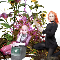 Grimes, in an orange wig, sits amid a field of flowers.