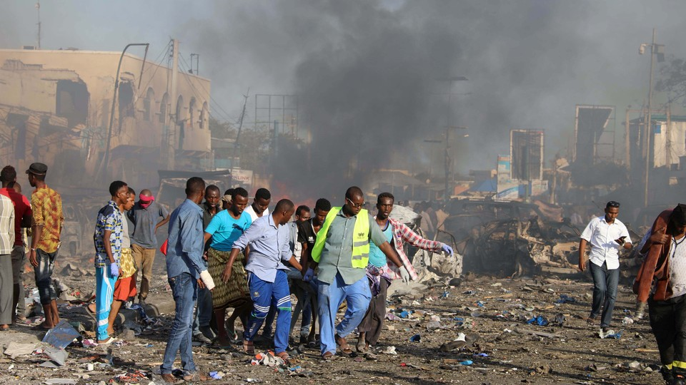 Civilians carry the dead body of an unidentified man from the scene of an explosion.