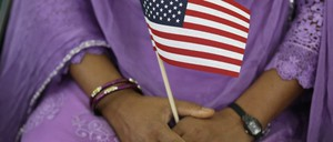 A South Asian woman holds an American flag during a naturalization ceremony in Indianapolis.