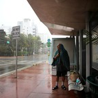 A man shelters from the rain at a bus stop.