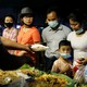 A family wearing face masks buys food from a stall in Yangon, Myanmar.
