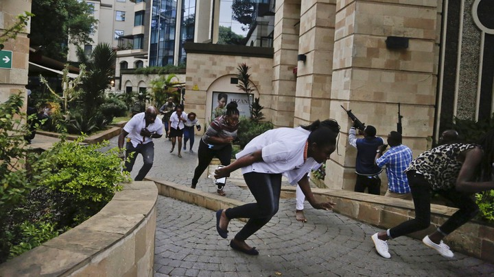 Civilians run with their heads down from the Nairobi hotel complex where terrorists killed at least 14 people on Tuesday.