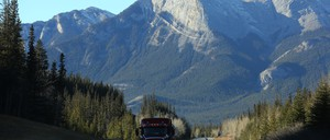 A truck drives along a highway out of the Rocky Mountains.