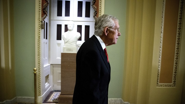Former Senate Majority Leader Harry Reid walks in a hallway in the Capitol.