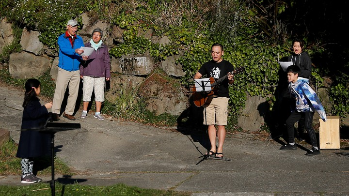"""Yee Feng sings """"Keep Your Head Up"""" by Andy Grammer with wife, Carolyn, and kids Ellie, 9, and Jediah, 11, during a neighborhood sing-along they have started doing each evening to connect with neighbors while social distancing during the coronavirus outbreak in Seattle."""