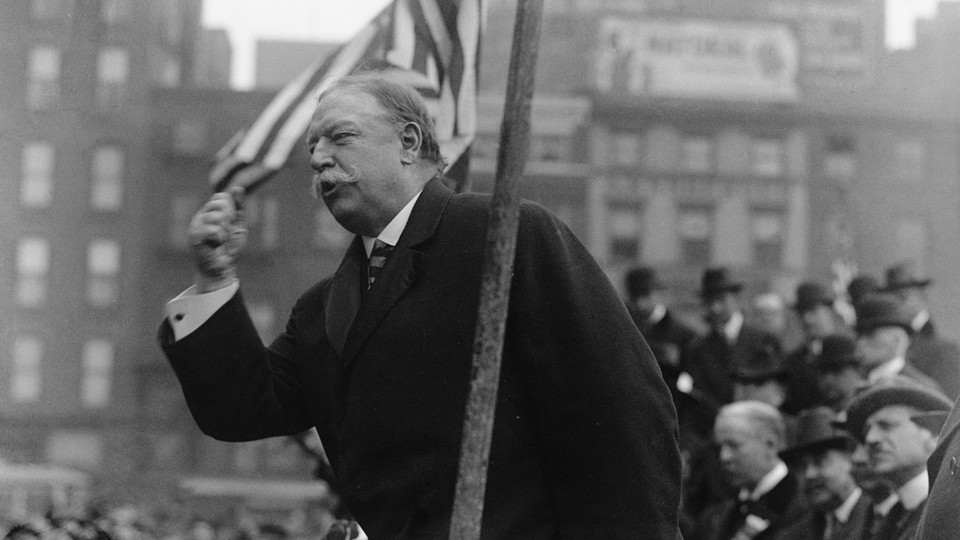 Former President William Howard Taft speaks at a campaign rally, with the American flag waving behind him.