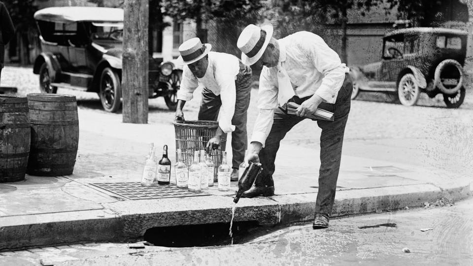 Two men pour liquor down a storm drain during the Prohibition era