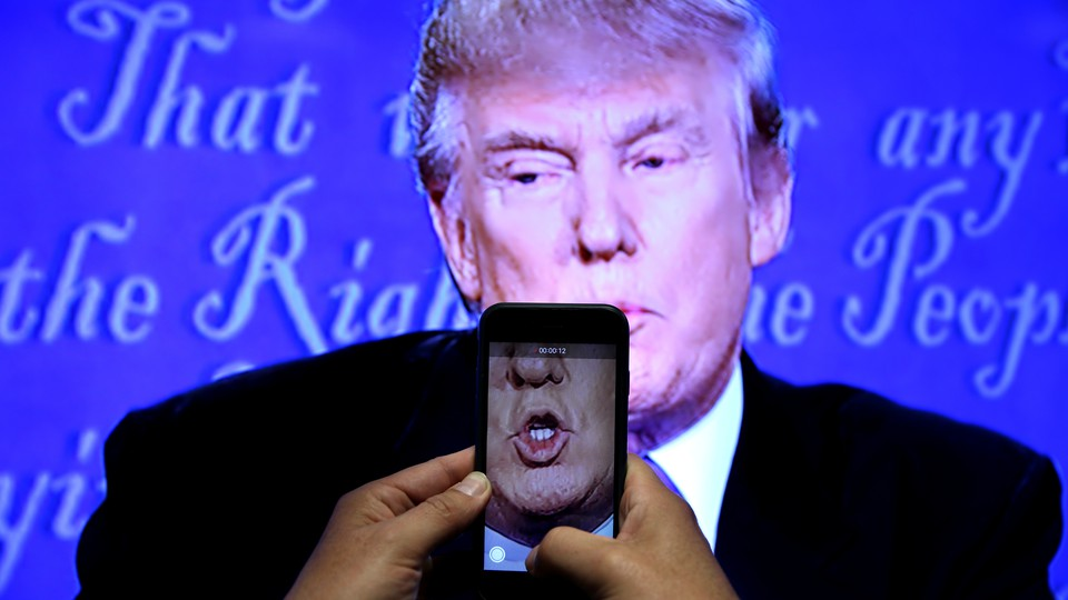 A journalist records a video from screen as Republican U.S. presidential nominee Donald Trump speaks during the first presidential debate with U.S. Democratic presidential candidate Hillary Clinton at Hofstra University.