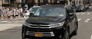 A car with an Uber logo rolls down a New York City street.