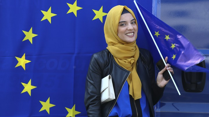 A Muslim woman holds a European flag during a pro-EU demonstration.