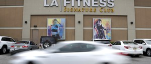 A car driving past a New Jersey location of LA Fitness.