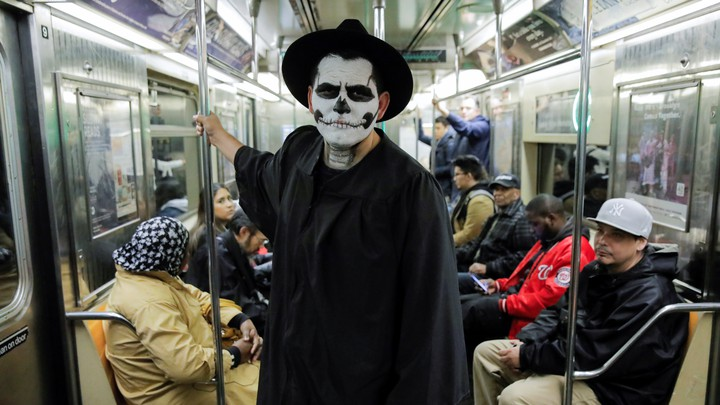 A man rides the subway dressed as a skeleton