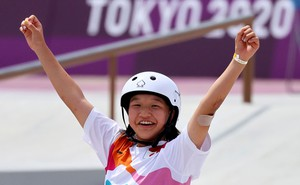 A young skateboarder raises her arms in celebration.
