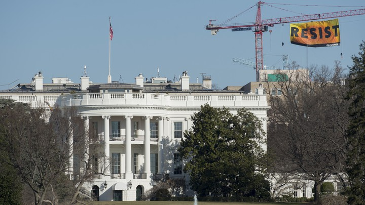 A construction crane with a sign reading RESIST stands behind the White House.