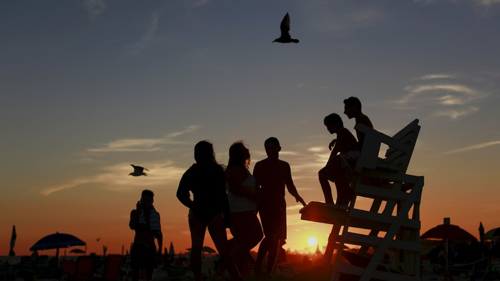 Kids are seen in silhouette at sunset on the beach in Atlantic Beach, New York, on September 6, 2015.