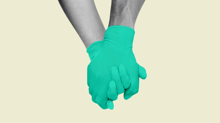 Two holding hands wearing green gloves
