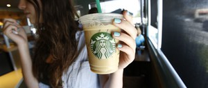 A woman holds an iced drink with a plastic straw at a Starbucks location.