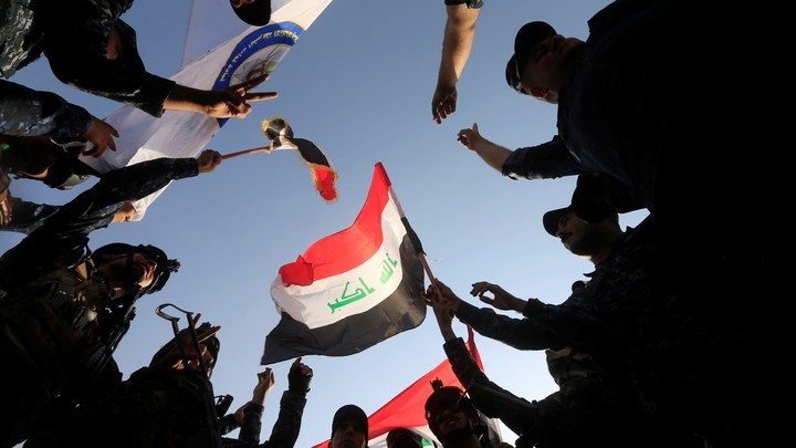 Circle of Iraqi soldiers celebrate as they waive an Iraqi flag.