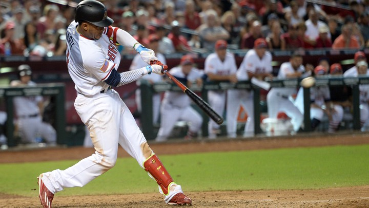 A professional baseball player hits a ball with his bat during the ninth inning.
