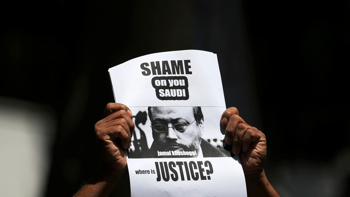 """A protestor holds a sign that reads, """"Shame on you Saudi. Where is justice?"""""""