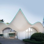 A curvy, one-story white building from the 1960s with glass walls and teal trim located in Naugatuck, Connecticut.
