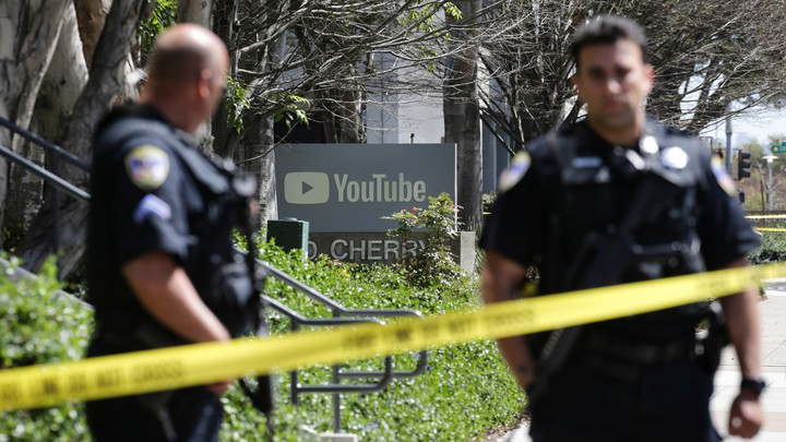 Police officers stand guard outside YouTube headquarters.