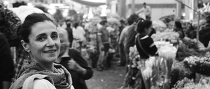 Black and white photo of a smiling woman at the market.