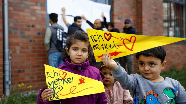 "Two Syrian children hold up signs reading ""Ich Merkel."""