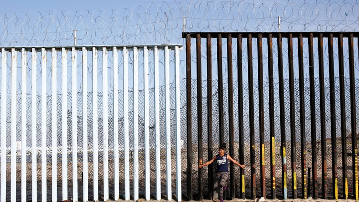 A woman leans against the U.S.-Mexico border wall