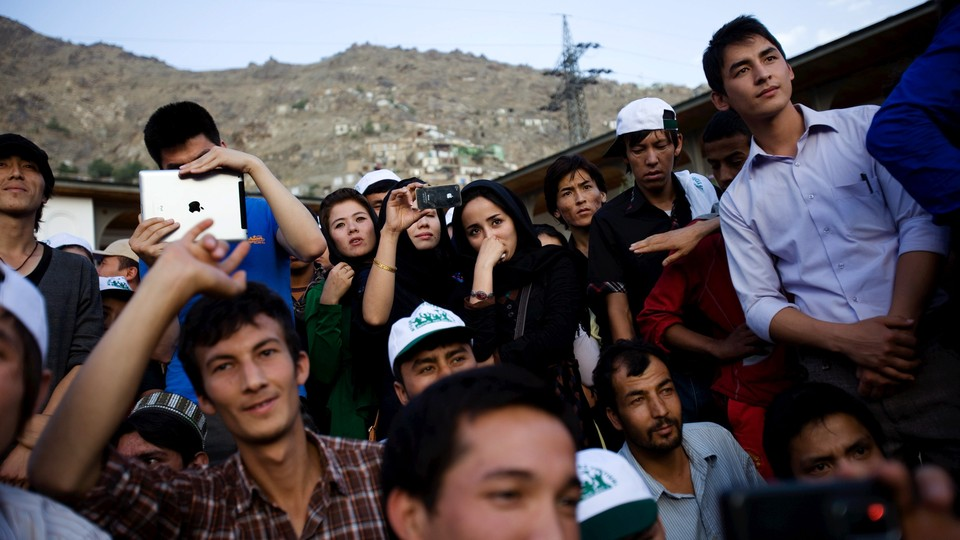 Young Afghan men and women listen to a concert in Kabul.
