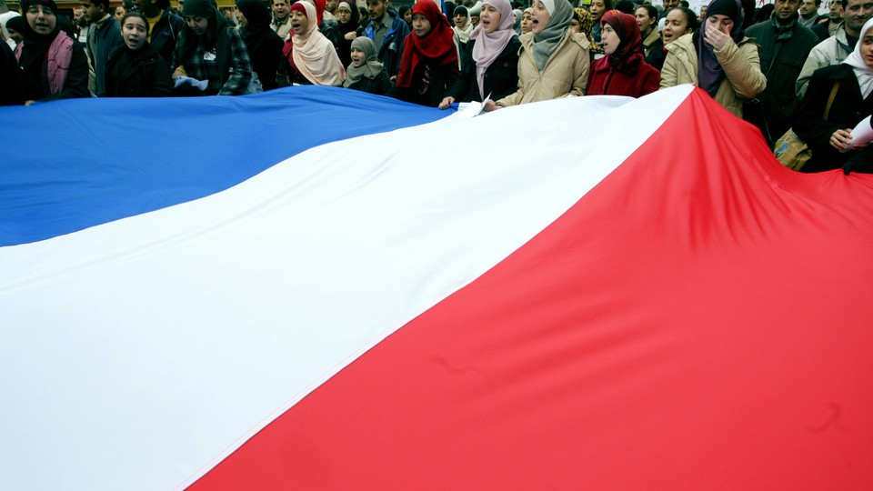 Women wearing head scarves carry the French national flag during a demonstration.