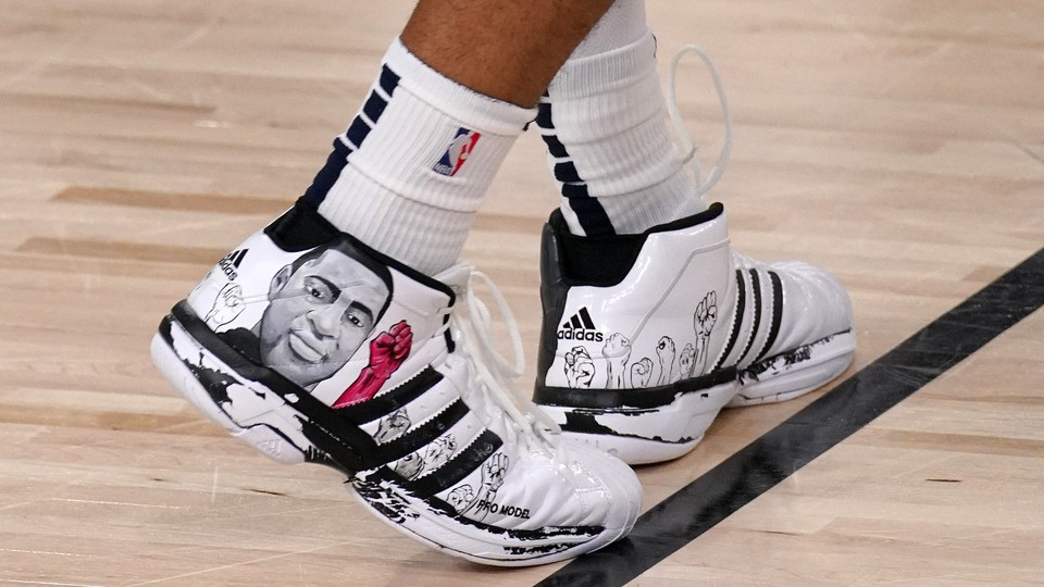 A pair of basketball shoes with George Floyd drawn on them.