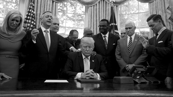 President Trump, Vice President Mike Pence, and faith leaders say a prayer in the Oval Office in September 2017. Several people have their hands on Trump's shoulders. Most of the people have their eyes closed.