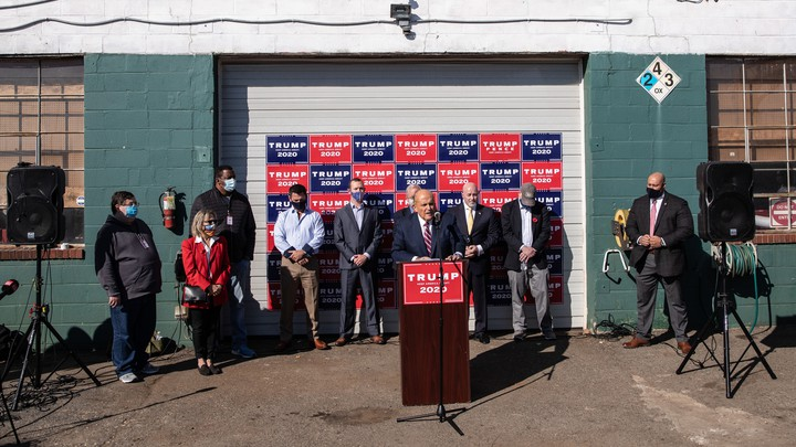 Rudy Giuliani holds a press conference outside a landscaping store.