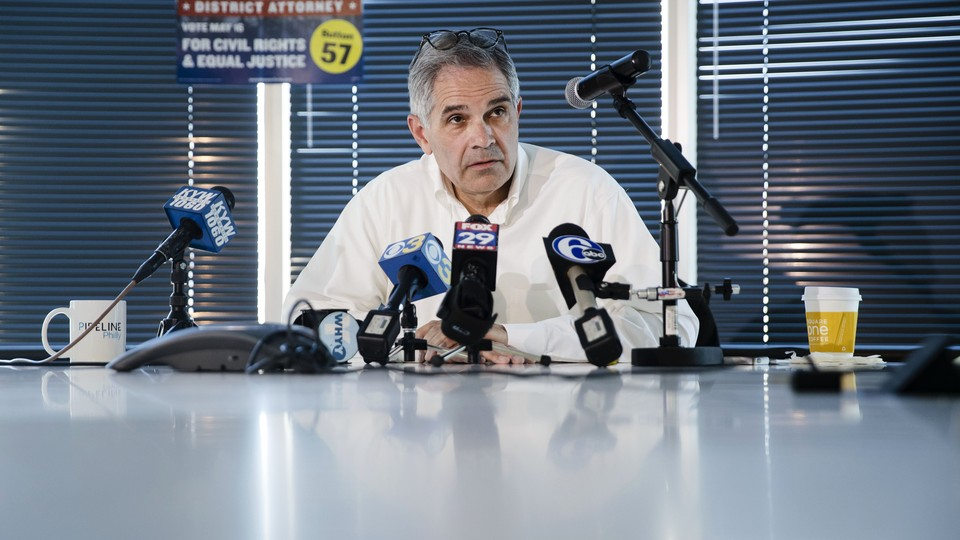 Larry Krasner, the Democratic candidate for district attorney in Philadelphia, sits at a table and speaks into multiple microphones during a news conference in May.