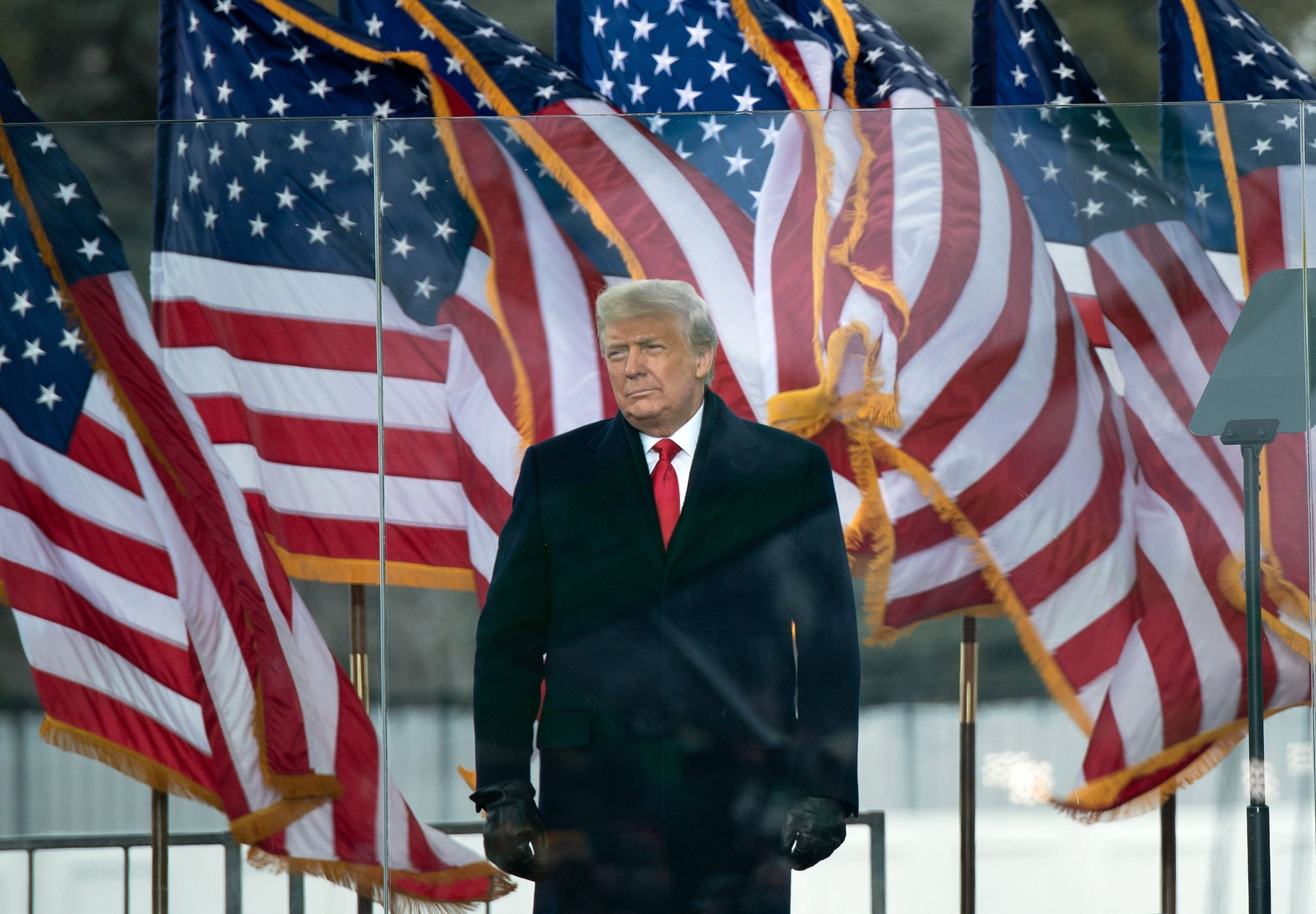 Donald Trump standing outside, behind clear barriers and in front of a row of billowing American flags