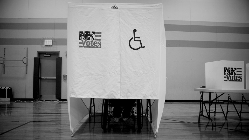 A person using a wheelchair votes at a wheelchair-accessible voting booth.