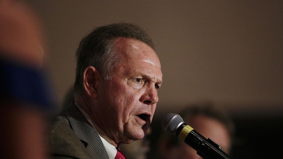 Former Alabama chief justice and U.S. Senate candidate Roy Moore speaks into a microphone during his election party on September 26.