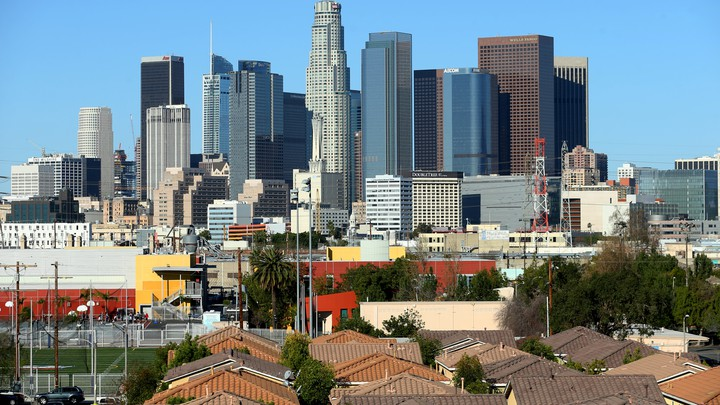 Single-family homes sit in front of the Los Angeles skyline
