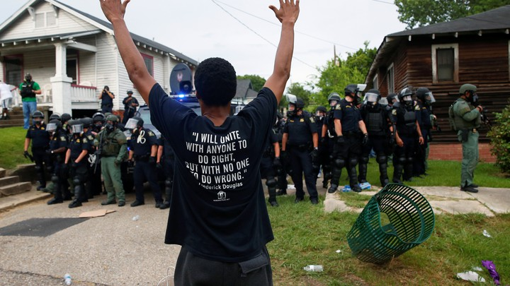 A demonstrator raises his hands in front of police in riot gear during protests in Baton Rouge, Louisiana, U.S., July 10, 2016.