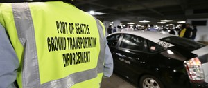 On March 31, 2016, a transportation enforcement worker watches ride-sharing vehicles pull into their spaces at Seattle-Tacoma International Airport, the first day they could legally pick up and drop off customers there.