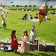 A birthday party in a park on a sunny day, with people relaxing in the background an urban skyline in the distance