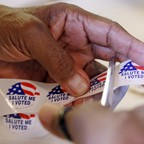 """Hands clipping """"I Voted"""" stickers"""