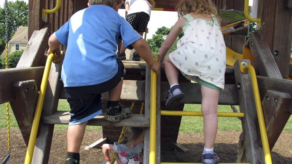 A boy and girl climb up a swing set.