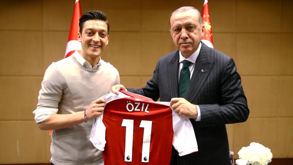 Özil and Erdoğan pose for a photo holding Özil's Arsenal jersey.