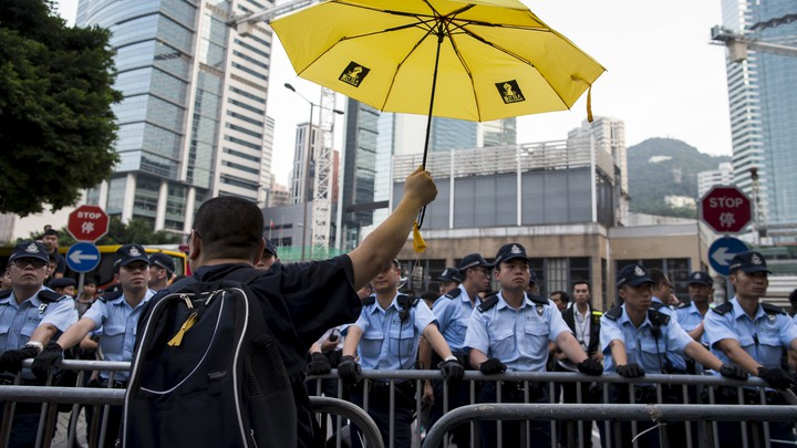 A pro-democracy protester rises a yellow umbrella, the symbol of the Occupy Central movement, in front of a line of police officers.