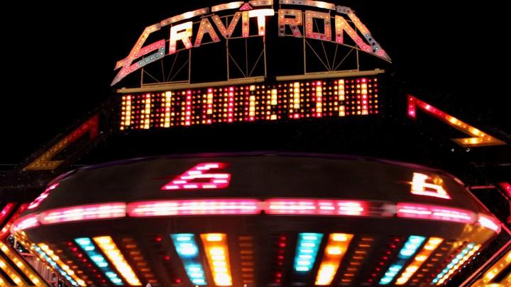 A gravitron ride at a carnival at night