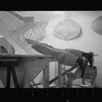 Black-and-white photo of an architect's legs sticking out of his large tabletop model of an airport.