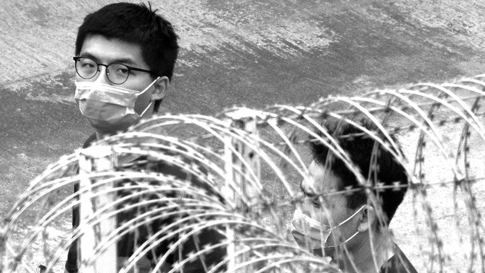 Two men wearing surgical masks walk behind a barbed-wire fence.