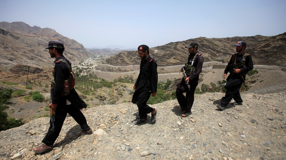Four Pakistani security personnel patrol the border with Afghanistan